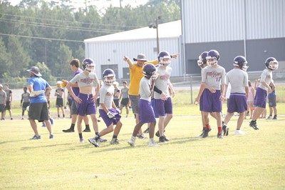Poyen Head Football Coach Vick Barrett guides the offense to the line for a play during the Small Town Shootout 7-on-7 tournament at Poyen on Friday, June 8.